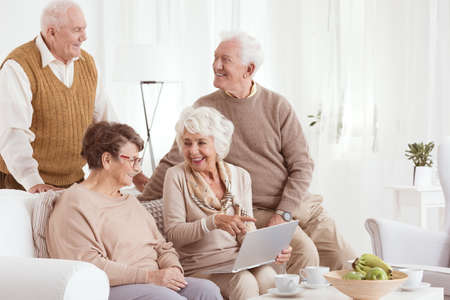 Group of elderly people using new technology in retirement club