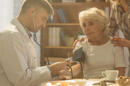 Handsome doctor checking his older patient's blood pressure