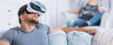 Young man on a couch looking up with the VR glasses