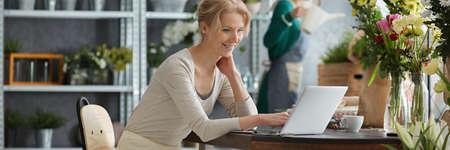 Photo pour Young blonde woman with laptop and flowers on the desk - image libre de droit