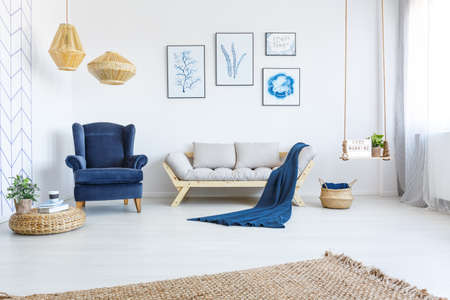 Photo pour White home interior with sofa, armchair, posters, lamps and rug - image libre de droit