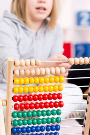 Little blonde girl learning to count using the colorful abacus