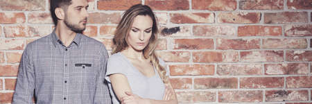 Passionate stylish young couple standing against brick wall