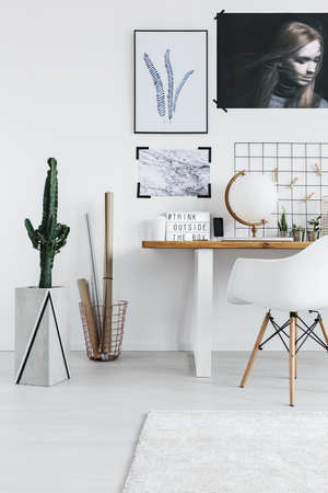 Stylish white room interior with desk, chair and cactus