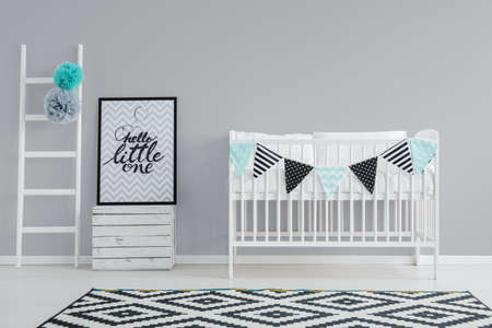 Photo pour Grey wall and white furniture in baby room - image libre de droit