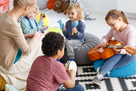 Photo pour Group of little children playing music in kindergarten - image libre de droit