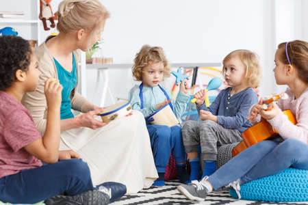 Photo pour Little kids in kindergarten playing instruments during music lesson - image libre de droit
