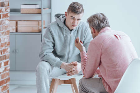 Rebellious teenager talking with counselor about his issues