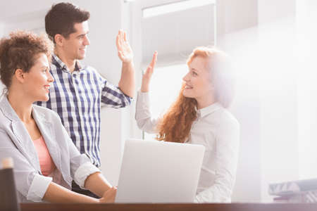 Successful business colleagues giving high five at desk in office