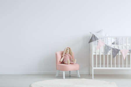 Photo pour Roomy children's bedroom with a white, circular carpet, a pink chic chair with a toy sitting on it, and a baby bed - image libre de droit