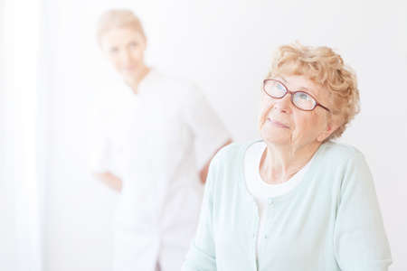 Smiling young nurse is looking at happy older women in glasses at her home