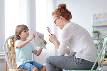 Adoptions counselor looking via magnifying glass on a picture of perfect home shown by an orphan boy