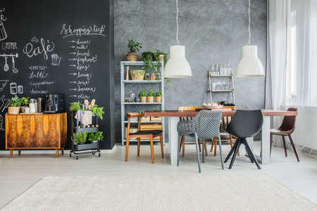 Chalkboard accents and mismatched chairs in eclectic dining room