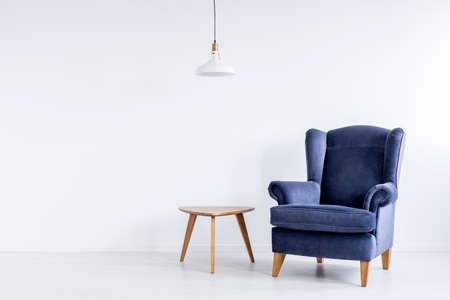 Photo pour White lamp above wooden table next to dark blue classic armchair in spacious white room - image libre de droit