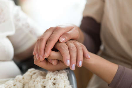Close-up photo of a female caregiver and senior woman holding hands. Senior care concept.
