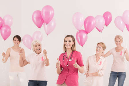 Smiling women and doctor in pink uniform holding pink balloons. Breast cancer concept