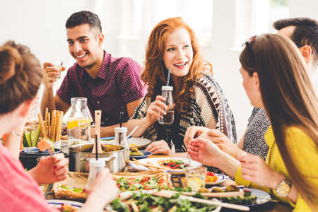 Photo pour Group of mixed-race people celebrating vegan party at home, sitting at colorful table full of healthy snacks, salads and organic dishes - image libre de droit