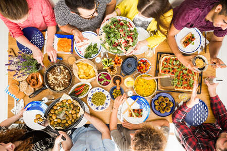 Slow food and lifestyle concept, top view of gathering of friends around the table with delicious vegan dishes