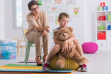Sad boy sitting on yellow pouf being turned back to the psychotherapist and hugs teddy bear