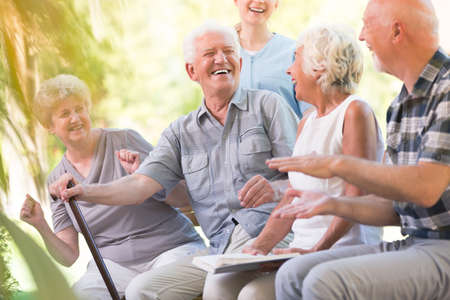 Photo pour Group of smiling senior friends spending time together sitting in the park - image libre de droit
