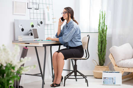 Virtual assistant sitting at home office and talking on the phone with her boss