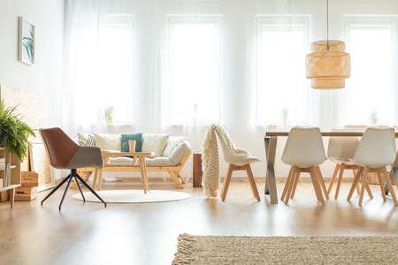 Foto de Vintage chair and sofa in multifunctional dining room with wooden table under lamp - Imagen libre de derechos