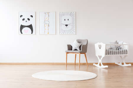 Photo pour Grey chair with pillow and white round rug near white crib in baby's room with animal posters on the wall - image libre de droit