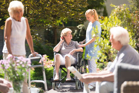 Photo pour Senior woman in wheelchair spending time outside, getting some fresh air with her nurse from rest home - image libre de droit