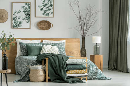 Photo pour Pillows and blanket on cabinet in khaki bedroom with wooden furniture and white pillow on bed - image libre de droit