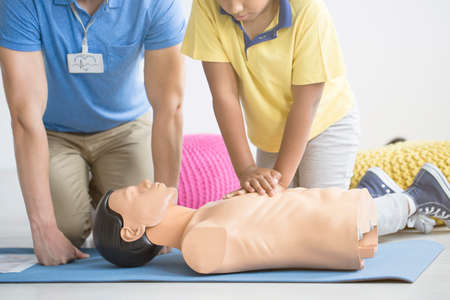 Afro-american boy reanimating a manikin during first aid training with paramedic