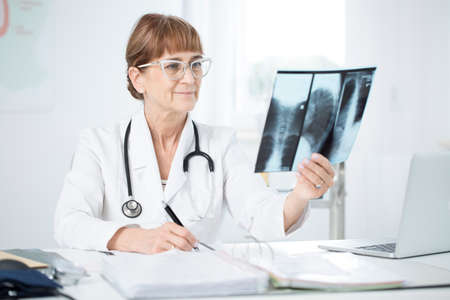 Pulmonologist with stethoscope looking at an X-ray picture of a cigarette smoker in an office with laptop