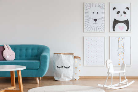 Photo pour Scandi design of bright kid room with white rocking horse, blue sofa and posters with animals - image libre de droit