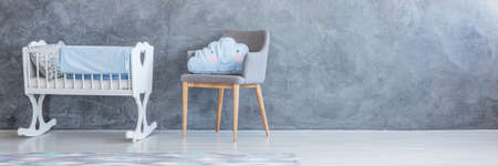 Blue cloud pillow on grey armchair next to white cradle with blue blanket against concrete wall with copy space in child\'s bedroom interior