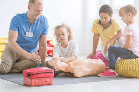 Boy practicing reanimation on manikin during first aid training in school with instructor