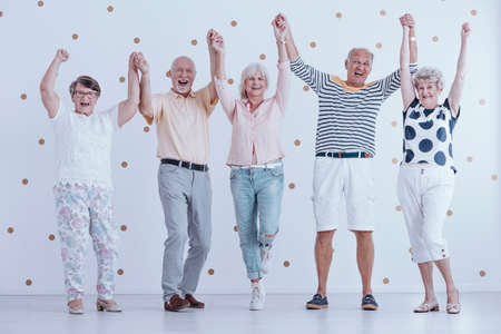 Photo pour Excited elders holding hands in the air and welcoming new year together - image libre de droit