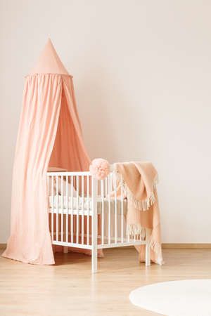 Photo pour Minimalist, white crib with a pastel pink canopy for a baby girl by a white, empty wall in a cute, modern nursery room interior - image libre de droit