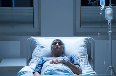 Woman dying of cancerous tumor in palliative ward, lying alone in bed with tubes