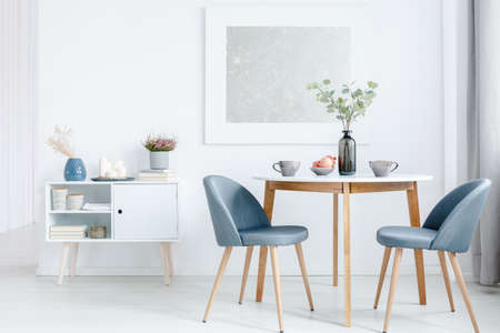 Photo for Small dining table with two upholstered chairs and a white cabinet in a bright, open space living room interior - Royalty Free Image