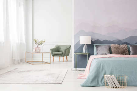 Photo pour Modern, golden frame coffee table with an elegant glass vase and a comfortable green armchair in a white studio interior with a large bed - image libre de droit