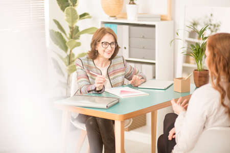 Photo for Smiling personal advisor talking to a client in her light, cozy office - Royalty Free Image