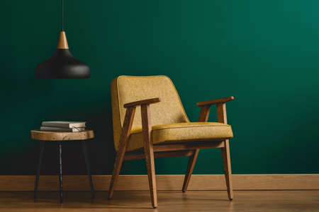 Foto de Yellow, vintage armchair, side table with books and black lamp set on the emerald wall in living room interior - Imagen libre de derechos