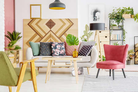 Photo pour Armchairs, sofa with patterned cushions and wooden wall in a living room interior - image libre de droit