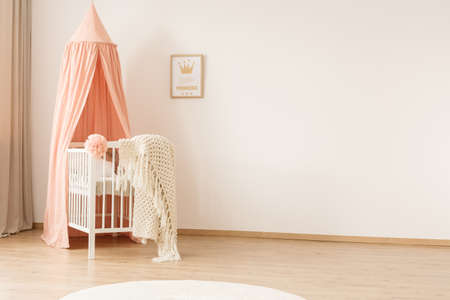 White woolen blanket and pastel pink pompom placed on a wooden crib with canopy in bright baby room interior with poster on the wall