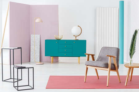 Wooden turquoise cupboard with gold bowl and white globe standing in pastel colors room interior with grey chair and metal lamp in the corner