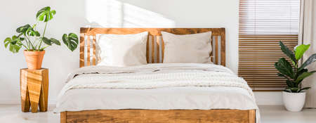 Photo pour Close-up of double wooden bed with bedding, pillows and blanket against white wall in a bright sunny bedroom interior. Two green plants standing beside. Panorama. Real photo. - image libre de droit