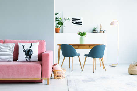 Real photo of an open space flat interior with a pink couch in the living area and a wooden table with gray chairs in the dining space