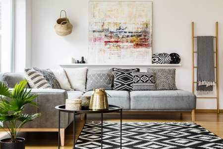 Photo for Patterned pillows on grey corner sofa in living room interior with table and painting. Real photo - Royalty Free Image