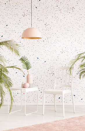 Pink lamp above white chair and table in bright living room interior with plants. Real photo