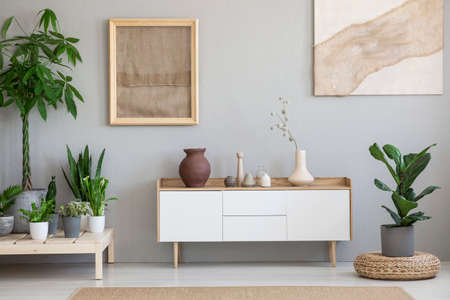 Posters on grey wall above white cupboard in living room interior with plants and pouf. Real photo