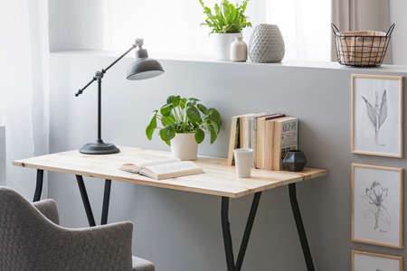 Photo pour Real photo of wooden desk with fresh plant, black lamp, coffee cup and books standing on half-wall with simple posters - image libre de droit
